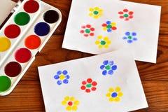 Due disegni con i fiori, pittura del dito, gioco dei bambini Vernice variopinta Priorità bassa di legno del Brown Fotografia Stock