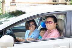 Due donna e bambini che conducono automobile con il fronte felice Immagini Stock