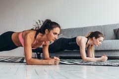 Due donne adatte che fanno la plancia si esercitano sul pavimento a casa che si prepara indietro e premono i muscoli, lo sport, a immagine stock
