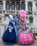 Due donne adorabili che tengono fan e che portano i costumi blu e rosa decorati dipinti a mano e del maschera al carnevale di Ven fotografia stock libera da diritti