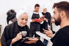 Due donne adulte con gli asciugamani sulle teste scelgono l'acconciatura che gli stilisti mostrano loro Immagine Stock Libera da Diritti