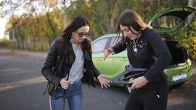 Due donne al bordo della strada che prova a cambiare una gomma dalla vostra automobile con un Jack, clouse su stock footage