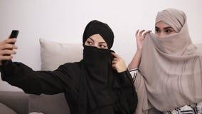 Due donne arabe nei hijabs - neri e nella seduta beige sul sofà grigio mentre prendendo l'immagine del selfie insieme a casa archivi video