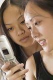 Due donne asiatiche che per mezzo del telefono delle cellule fotografia stock libera da diritti