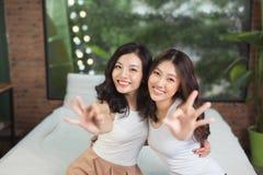 Due donne asiatiche nella camera da letto sul letto si divertono fotografia stock