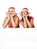 Due donne in cappello dell'assistente di Santa con lo spazio in bianco Fotografia Stock