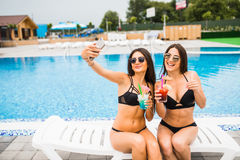 Due donne castane attraenti che portano bikini che posa vicino alla piscina, facente la foto del selfie Giovani adulti fotografia stock