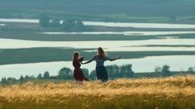 Due donne che ballano e che ridono nel campo di estate sui precedenti del lago video d archivio
