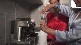 Due donne che chiacchierano nella cucina che va iniziare a bere vino rosso - un abito blu d'uso di mattina, l'altro abito rosso archivi video