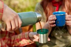 Due donne che dividono una boccetta termica di caffè Immagini Stock