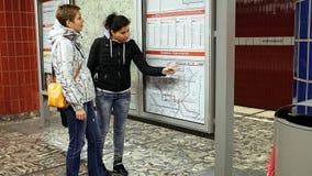 Due donne che esaminano la mappa della metropolitana del sottopassaggio Immagine Stock