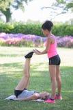 Due donne che fanno gli allenamenti delle gambe in parco Fotografie Stock Libere da Diritti