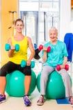 Due donne che fanno sport di forza nella palestra di forma fisica Fotografia Stock Libera da Diritti