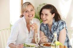 Due donne che hanno pasto in caffè Immagini Stock