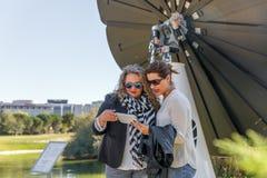 Due donne che indossano l'abbigliamento casual traggono le conclusioni mentre esaminano una compressa, in mezzo ad un parco tecno fotografia stock
