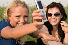 Due donne che leggono gli sms Fotografia Stock