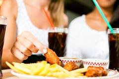 Due donne che mangiano le ali di pollo e che bevono soda Fotografia Stock