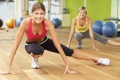 Due donne che partecipano alla classe di forma fisica della palestra Fotografia Stock