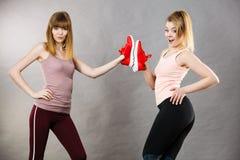 Due donne che presentano ad istruttori degli abiti sportivi le scarpe Immagine Stock