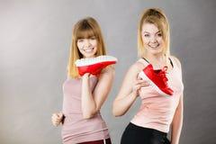 Due donne che presentano ad istruttori degli abiti sportivi le scarpe Fotografia Stock Libera da Diritti