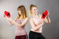 Due donne che presentano ad istruttori degli abiti sportivi le scarpe Immagini Stock