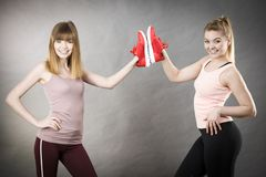 Due donne che presentano ad istruttori degli abiti sportivi le scarpe Immagini Stock Libere da Diritti