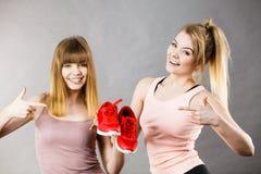 Due donne che presentano ad istruttori degli abiti sportivi le scarpe Fotografie Stock