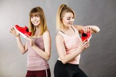 Due donne che presentano ad istruttori degli abiti sportivi le scarpe Immagine Stock Libera da Diritti