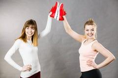 Due donne che presentano ad istruttori degli abiti sportivi le scarpe Fotografie Stock Libere da Diritti