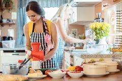 Due donne che producono le insalate nella cucina fotografia stock