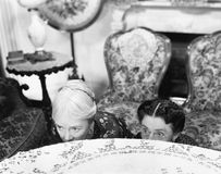 Due donne che si nascondono dietro una tavola e che esaminano il bordo (tutte le persone rappresentate non sono vivente più lungo Fotografie Stock Libere da Diritti