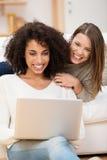 Due donne che si rilassano a casa con un computer portatile Fotografie Stock