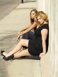 Due donne che si siedono il marciapiede Sunny Day del bordo immagine stock