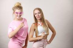 Due donne che tengono gli accessori di carnevale Immagine Stock