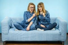 Due donne colpite che tengono gli occhiali falsi sul bastone Fotografia Stock