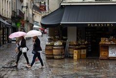 Due donne con gli ombrelli del ounder dei sacchetti della spesa fotografie stock libere da diritti