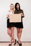 Due donne con il bordo in bianco Fotografie Stock Libere da Diritti