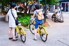 Due donne con le bici comuni sulla via in Cina immagini stock
