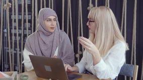 Due donne degli amici stanno considerando lo schermo del computer portatile nella sala e nella discussione video d archivio