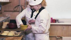 Due donne del cuoco divertendosi in una cucina video d archivio