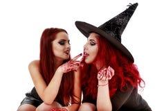 Due donne delle testarosse con la scena sanguinosa di Halloween delle mani Immagini Stock