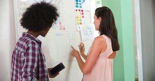 Due donne di affari che hanno riunione di 'brainstorming' in ufficio video d archivio