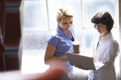 Due donne di affari che hanno riunione informale in ufficio Immagini Stock