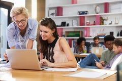 Due donne di affari che lavorano al computer portatile in ufficio occupato fotografia stock libera da diritti