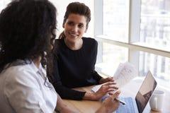 Due donne di affari che utilizzano computer portatile nella riunione dell'ufficio immagini stock