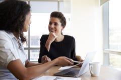 Due donne di affari che utilizzano computer portatile nella riunione dell'ufficio immagine stock libera da diritti