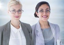Due donne di affari con il chiarore contro il pannello di legno grigio confuso Immagini Stock Libere da Diritti