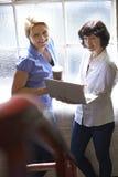 Due donne di affari con il computer portatile che ha riunione informale in ufficio immagini stock libere da diritti