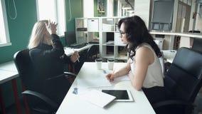 Due donne di affari discutono lavorare le edizioni in ufficio facendo uso dei documenti e della compressa stock footage