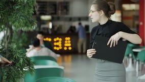 Due donne di affari nel self-service durante una pausa di lavoro, un caffè bevente e la discussione delle edizioni di affari video d archivio